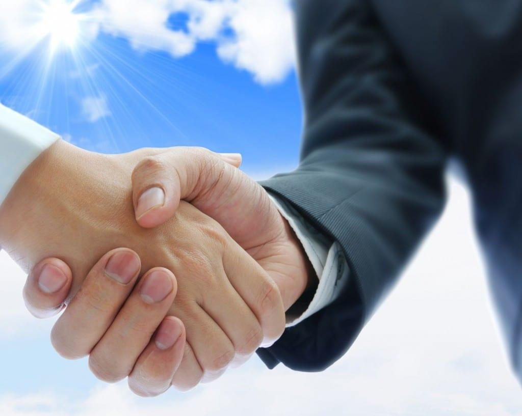 hand shake with blue skies